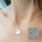 Silver necklace with engraved kid drawing on a disc